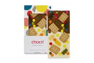 """chocri weiße und Vollmilchschokoladentafel """"Kinderlachen"""" mit Schokolinsen, Butterkekse und Gummibären in der Verpackung und einzelnd davor stehend"""