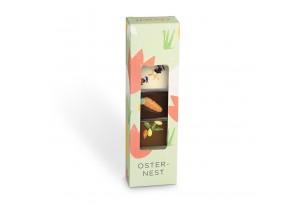 """chocri kleine Weltreise """"Osternest"""" aus Zartbitter-,Vollmilch und weiße Schokoladentafeln mit österlichen Zutaten wie Marzipan-Möhre in der Verpackung verpackt"""