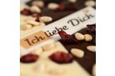 chocri weiße und Zartbitterschokoladentafel in Herzform mit Cranberries und Pinienkerne und einem 'Ich liebe Dich' Schriftzug Nahaufnahme,Detailansicht