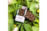 chocri Vollmilchschokoladentafel 'Chill in Green' mit Minze, Honigschokoladentropfen und Johannisbeeren in einer Faultier-Verpackung und einzelnd im Wald liegend