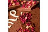 chocri 'Danke' XXL-Gruß-Schokoladentafel in einer Holzkiste handbeschriftet und dekoriert mit Himbeeren, Heidelbeeren, Bourbon Vanille und Karamellstücken in Detailansicht gebrochene Stücken
