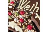 chocri 'Frohe Weihnachten' XXL-Gruß-Schokoladentafel in Holzkiste handbeschriftet und dekoriert mit Pistazien, Haselnusskrokant, Johannisbeeren und Kokos im Detailansicht