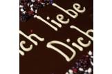 chocri 'FIch liebe Dich' XXL-Gruß-Schokoladentafel in Holzkiste handbeschriftet und dekoriert mit dragierten Schokoherzen, Brombeeren, Joghurtcrisp und dragierten Veilchenblüten in Detailansicht auf die Beschriftung