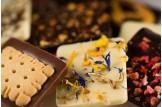 chocri Zartbitter-,Vollmilch und weiße Schokoladentafeln mit verschiedenen, internationalen Zutaten wie Butterkeks, Blütenmix oder Beeren Nahaufnahme, Detailansicht