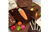 chocri kleine Weltreise 'Osternest' aus Zartbitter-,Vollmilch und weiße Schokoladentafeln mit österlichen Zutaten wie Marzipan-Möhre Naufaufnahme, Detailansicht