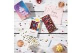 chocri 'Knusper Konfetti' Gaburtstagstafel aus Vollmilch-Schokoladentafel mit Kerzenhalter, Kerze, Schokolinsen, Himbeeren und Knusperperlen auf einem Tisch mit Grußkarte und Deko