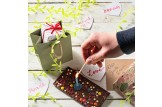 chocri 'Knusper Konfetti' Gaburtstagstafel aus Vollmilch-Schokoladentafel mit Kerzenhalter, Kerze, Schokolinsen, Himbeeren und Knusperperlen auf einem Tisch mit Kerze, die angezündet wird