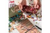chocri 'Knusper Konfetti' Gaburtstagstafel aus Vollmilch-Schokoladentafel mit Kerzenhalter, Kerze, Schokolinsen, Himbeeren und Knusperperlen auf einem Tisch mit brennender Kerze