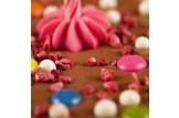 chocri 'Knusper Konfetti' Vollmilch-Schokoladentafel mit Kerzenhalter, Kerze, Schokolinsen, Himbeeren und Knusperperlen im Detailansicht