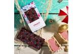 chocri Zartbitterschokoladentafel mit Sauerkirschen, Himbeeren, Glanzperlen und Veilchenbruch in einer Meerjungfrau-Verpackung und einzelnd am Strand liegend