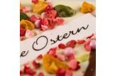 chocri weiße und Vollmilchschokoladentafel mit Erdbeer- und Joghurt-Maracuja-Stücken, Pistazien und einem 'Frohe Ostern' Aufleger Nahaufnahme, Detailansicht