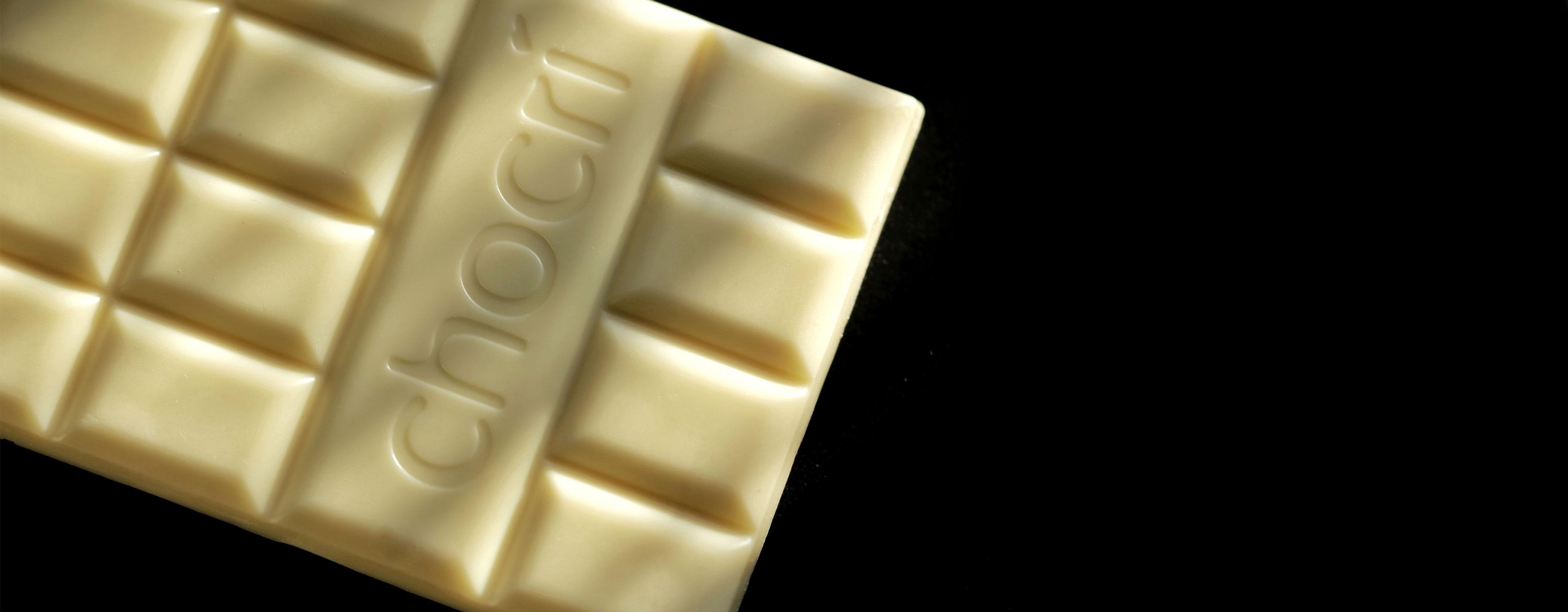 Weiße Schokoladentafel von chocri mit Logo auf der Rückseite auf einem schwarzem Hintergrund