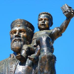 Bild vom großen Bischof Nikolaus von Myra mit beschenktem Kind als katholische Bronzetatue