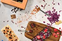 Die Vogelperspektive auf den Arbeitsplatz eines unserer Chocolatiers gleicht nicht nur einer herrlichen Zutatenexplosion, sondern zeigt auch, mit welcher Hingabe wir frisch für Dich kreieren und produzieren
